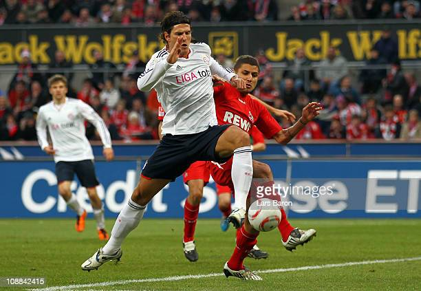 Mario Gomez of Muenchen is challenged by Youssef Mohamad of Koeln during the Bundesliga match between 1 FC Koeln and FC Bayern Muenchen at...