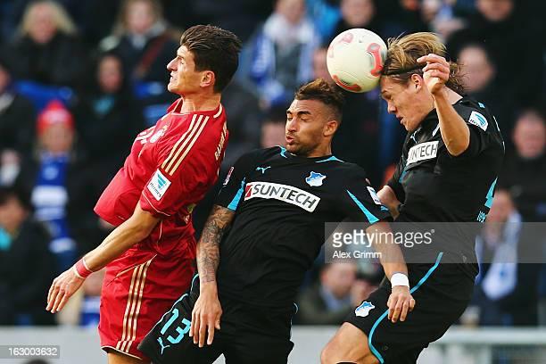 Mario Gomez of Muenchen jumps for a header with Daniel Williams and Jannik Vestergaard of Hoffenheim during the Bundesliga match between TSG 1899...