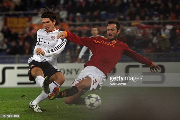 Mario Gomez of Muenchen scores his team's first goal against Marco Cassetti of Roma during the UEFA Champions League group E match between AS Roma...