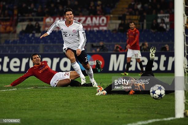 Mario Gomez of Muenchen scores his team's second goal against Nicolas Burdisso and goalkeeper Julio Sergio of Roma during the UEFA Champions League...