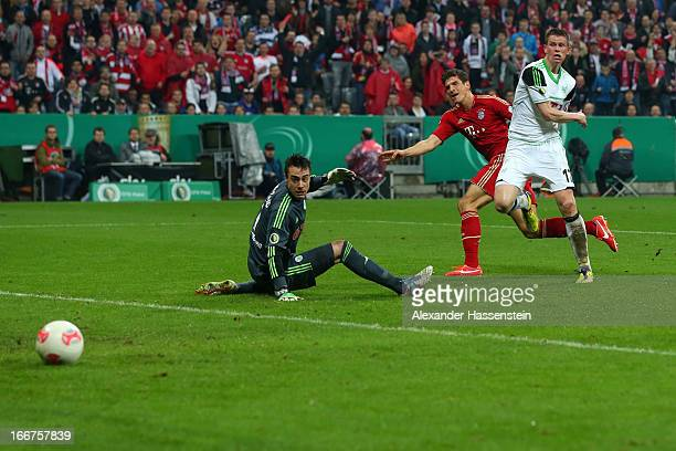 Mario Gomez of Muenchen scores the 5th team goal against Alexander Madlung of Wolfsburg and his keeoer Diego Benaglio during the DFB Cup Semi Final...