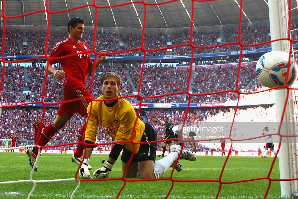 Mario Gomez of Muenchen scores the 5th team goal against Oliver Baumann, keeper of Freiburg during the Bundesliga match between FC Bayern Muenchen and SC Freiburg at Allianz Arena on September 10, 2011 in Munich, Germany.