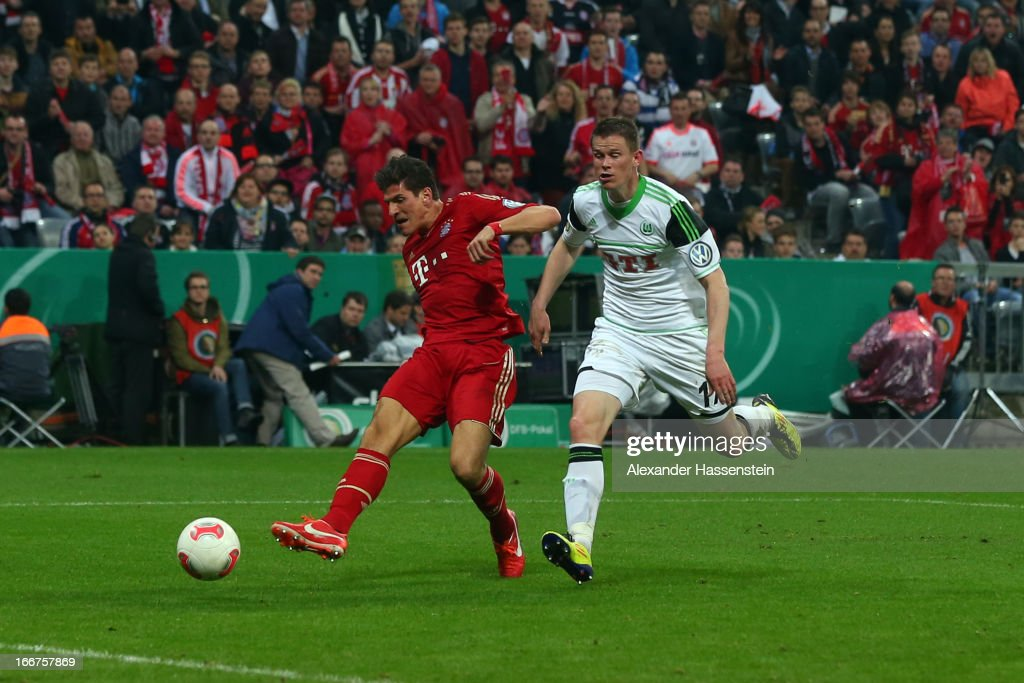 Mario Gomez (L) of Muenchen scores the 6th team goal against Alexander Madlung of Wolfsburg during the DFB Cup Semi Final match between Bayern Muenchen and VfL Wolfsburg at Allianz Arena on April 16, 2013 in Munich, Germany.
