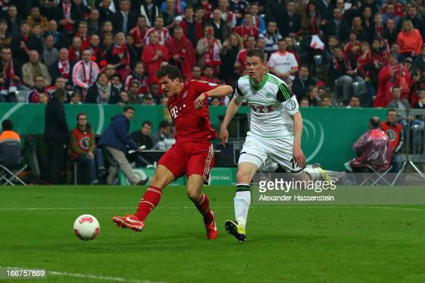 Mario Gomez of Muenchen scores the 6th team goal against Alexander Madlung of Wolfsburg during the DFB Cup Semi Final match between Bayern Muenchen...