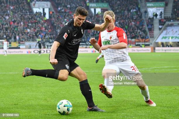 Mario Gomez of Stuttgart and Martin Hinteregger of Augsburg compete for the ball during the Bundesliga match between FC Augsburg and VfB Stuttgart at...