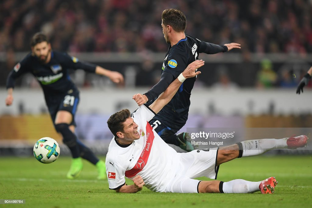 Mario Gomez of Stuttgart (bottom) fights for the ball with Niklas Stark of Berlin who then scores an own goal to make it 1:0 during the Bundesliga match between VfB Stuttgart and Hertha BSC at Mercedes-Benz Arena on January 13, 2018 in Stuttgart, Germany.
