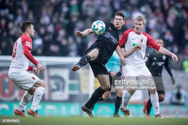 Mario Gomez of Stuttgart is tackled by Martin Hinteregger of Augsburg during the Bundesliga match between FC Augsburg and VfB Stuttgart at WWKArena...
