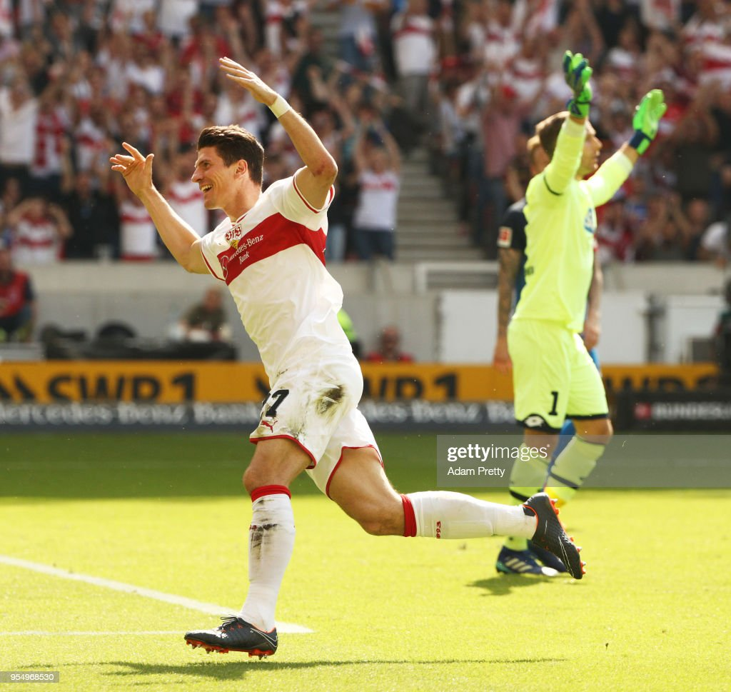 Mario Gomez of VfB Stuttgart celebrates after scoring the first goal while Oliver Baumann of 1899 Hoffenheim is dejected during the Bundesliga match between VfB Stuttgart and TSG 1899 Hoffenheim at Mercedes-Benz Arena on May 5, 2018 in Stuttgart, Germany.