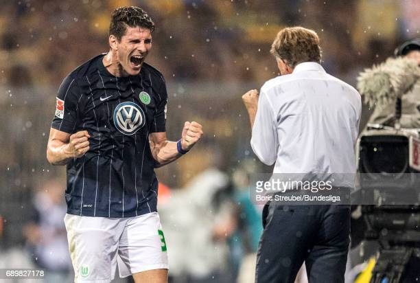 Mario Gomez of VfL Wolfsburg and head coach Andries Jonker of VfL Wolfsburg celebrate the continuance in the first Bundesliga after winning the...
