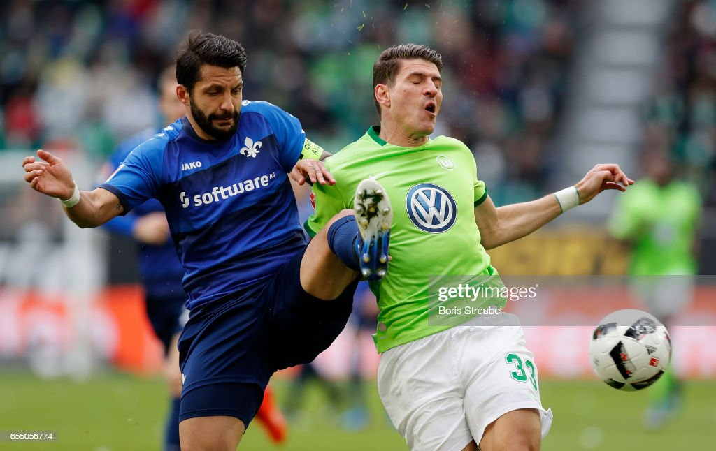 Mario Gomez of VfL Wolfsburg is challenged by Aytac Sulu of SV Darmstadt 98 during the Bundesliga match between VfL Wolfsburg and SV Darmstadt 98 at Volkswagen Arena on March 18, 2017 in Wolfsburg, Germany.