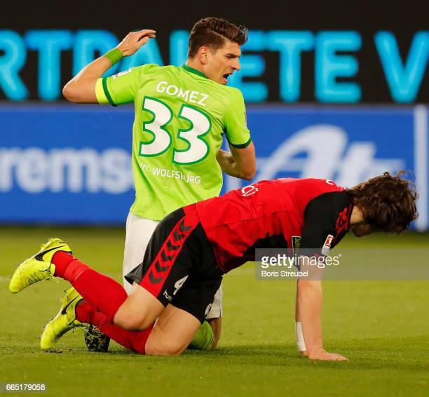 Mario Gomez of VfL Wolfsburg reacts with Caglar Soeyuencue of Freiburg during the Bundesliga match between VfL Wolfsburg and SC Freiburg at...