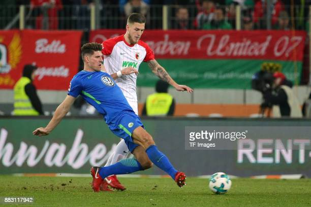 Mario Gomez of Wolfsburg and Jeffrey Gouweleeuw of Augsburg battle for the ball during the Bundesliga match between FC Augsburg and VfL Wolfsburg at...