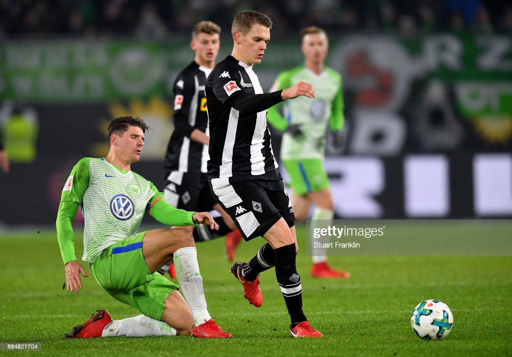 Mario Gomez (L) of Wolfsburg and matthias Ginter of Moenchengladbach battle for the ball during the Bundesliga match between VfL Wolfsburg and Borussia Moenchengladbach at Volkswagen Arena on December 3, 2017 in Wolfsburg, Germany.