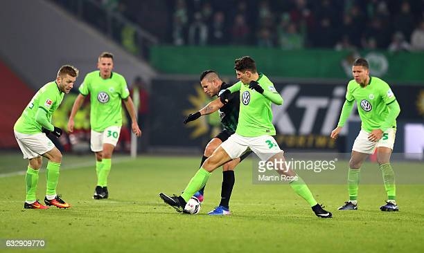 Mario Gomez of Wolfsburg and Raul Bobadilla of Augsburg battle for the ball during the Bundesliga match between VfL Wolfsburg and FC Augsburg at...