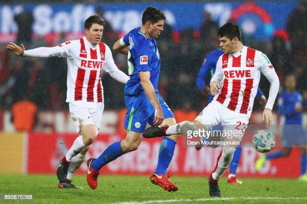 Mario Gomez of Wolfsburg battles for the ball with Dominique Heintz and Jorge Mere of FC Koeln during the Bundesliga match between 1 FC Koeln and VfL...