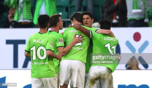 Mario Gomez of Wolfsburg celebrates after scoring his team's opening goal with team mates during the Bundesliga Playoff first leg match between VfL...