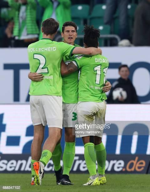 Mario Gomez of Wolfsburg celebrates after scoring his team's opening goal with Philipp Wollscheid and Daniel Didavi of Wolfsburg during the...