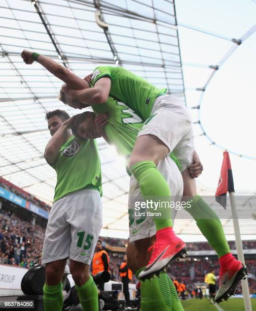 Mario Gomez of Wolfsburg celebrates scoring his third goal with Robin Knoche and Maximilian Arnold during the Bundesliga match between Bayer 04...
