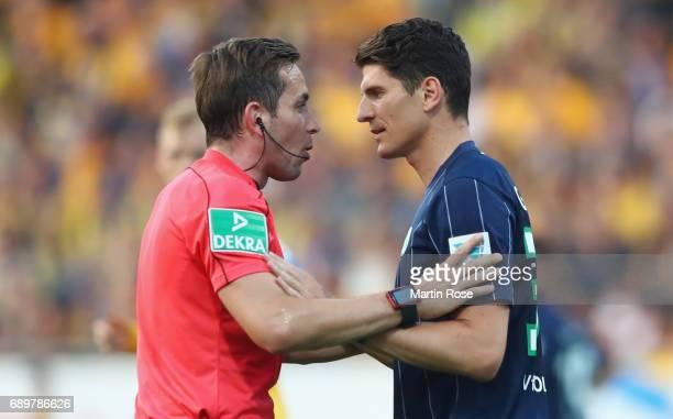 Mario Gomez of Wolfsburg discusses with referee Tobias Stieler during the Bundesliga Playoff leg 2 match between Eintracht Braunschweig and VfL...