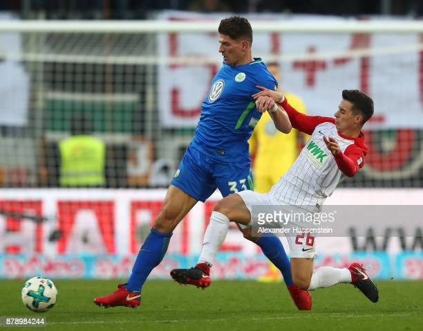 Mario Gomez of Wolfsburg fights for the ball with Erik Thommy of Augsburg during the Bundesliga match between FC Augsburg and VfL Wolfsburg at...