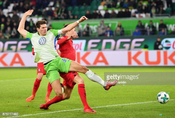 Mario Gomez of Wolfsburg is challenged by Robin Koch of Freiburg during the Bundesliga match between VfL Wolfsburg and SportClub Freiburg at...