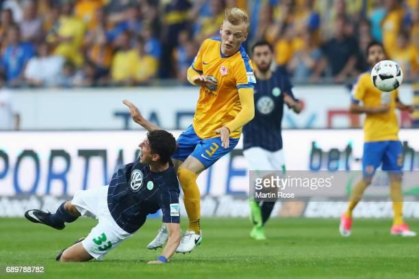 Mario Gomez of Wolfsburg is challenged by Saulo Decarli of Braunschweig during the Bundesliga Playoff leg 2 match between Eintracht Braunschweig and...