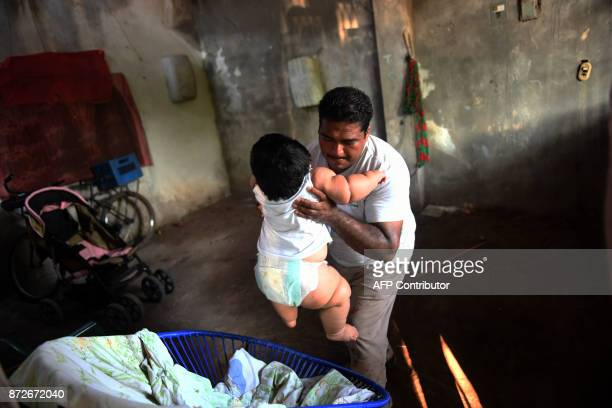 Mario Gonzales lifts his tenmonthold baby Luis at their home in Tecoman Colima state Mexico on November 8 2017 Luis Manuel Gonzales is almost like...