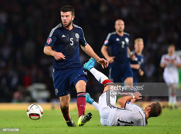 Mario Gotz of Germany is tackled by Grant Hanley of Scotland during the EURO 2016 Qualifier between Scotland and Germany at Hamden Park on September...