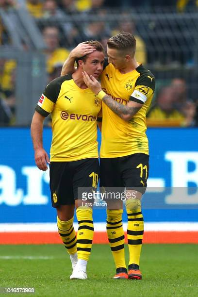 Mario Gotze of Borussia Dortmund celebrates with teammate Marco Reus after scoring his team's third goal during the Bundesliga match between Borussia...
