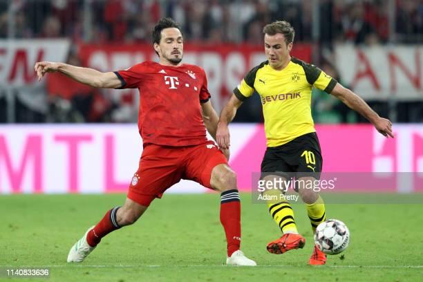 Mario Gotze of Borussia Dortmund is challenged by Mats Hummels of Bayern Munich during the Bundesliga match between FC Bayern Muenchen and Borussia...