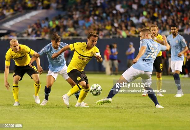 Mario Gotze of Borussia Dortmund vies for the ball against Luke Bolton of Manchester City in the first half of an International Champions Cup match...