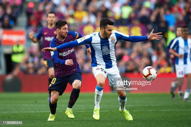 Mario Hermoso of RCD Espanyol and Lionel Messi of FC Barcelona compete for the ball during the La Liga match between FC Barcelona and RCD Espanyol at...