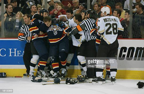Mario Lemieux of the Pittsburgh Penguins back center is restrained by linesman Ray Scapinello after a fight with Brad Ference of the Florida Panthers...