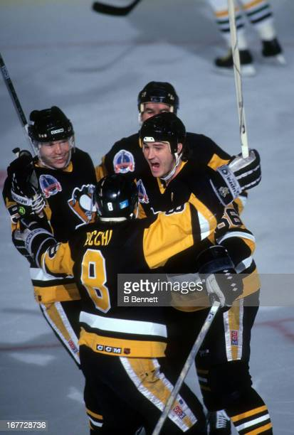 Mario Lemieux of the Pittsburgh Penguins celebrates with teammates Mark Recchi and Ulf Samuelsson during an 1991 Stanley Cup Finals game against the...