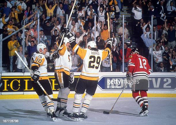 Mario Lemieux of the Pittsburgh Penguins celebrates with teammates Ron Francis and Phil Bourque as Brent Sutter of the Chicago Blackhawks skates by...