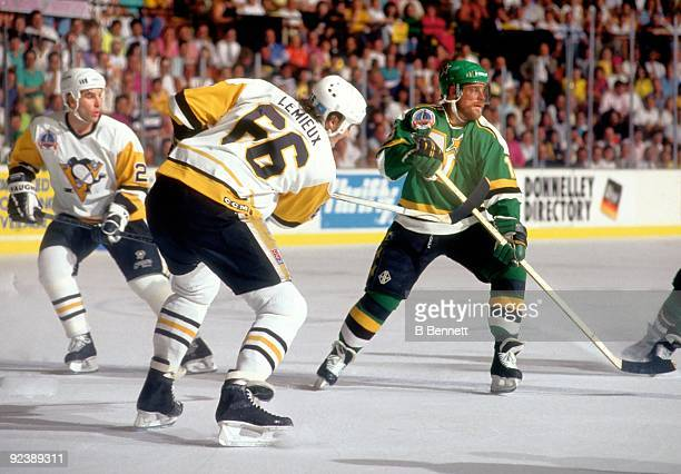Mario Lemieux of the Pittsburgh Penguins clears the puck as Dave Gagner of the Minnesota North Stars defends during Game 1 of the 1991 Stanley Cup...