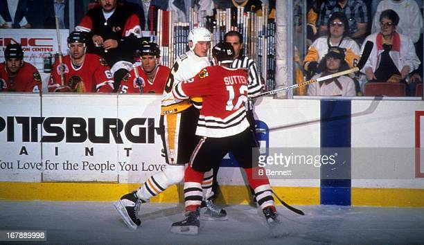 Mario Lemieux of the Pittsburgh Penguins is checked by Brent Sutter of the Chicago Blackhawks during Game 2 of the 1992 Stanley Cup Finals on May 28,...
