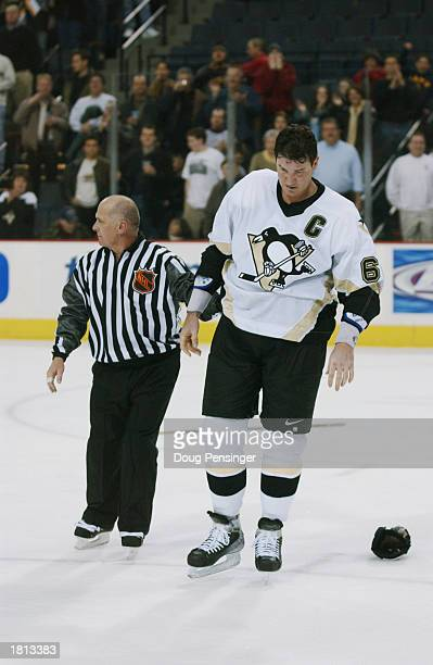 Mario Lemieux of the Pittsburgh Penguins is led from the ice by linesman Ray Scapinello after a fight with Brad Ference of the Florida Panthers at...