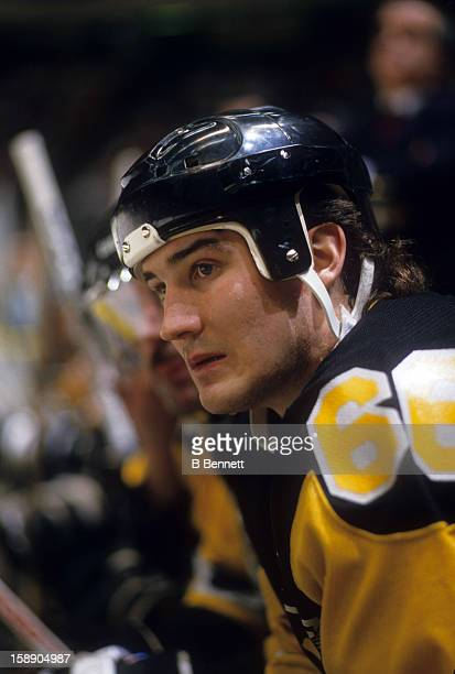 Mario Lemieux of the Pittsburgh Penguins looks on from the bench during an NHL preseason game in September 1989