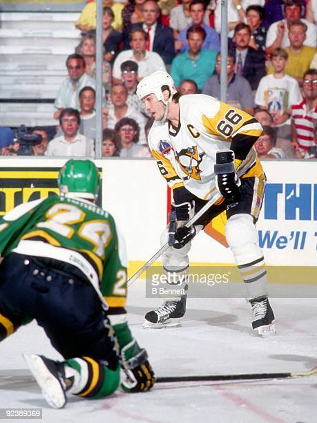 Mario Lemieux of the Pittsburgh Penguins looks to pass as Mark Tinordi of the Minnesota North Stars defends during Game 5 of the 1991 Stanley Cup...