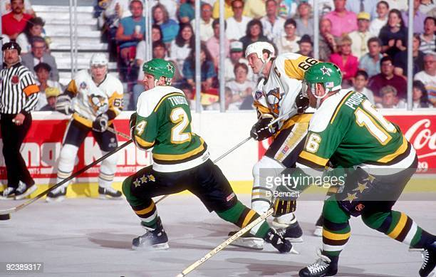 Mario Lemieux of the Pittsburgh Penguins shoots as Mark Tinordi and Brian Propp of the Minnesota North Stars defend during Game 1 of the 1991 Stanley...