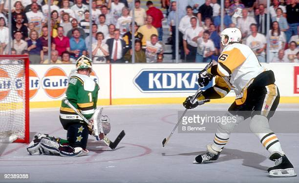 Mario Lemieux of the Pittsburgh Penguins shoots on a breakaway as goalie Brian Hayward of the Minnesota North Stars tries to make the save during...