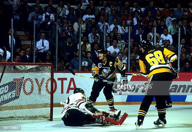 Mario Lemieux of the Pittsburgh Penguins shoots the puck to the top of the net while teammate Jaromir Jagr looks for a rebound as goalie Ed Belfour...
