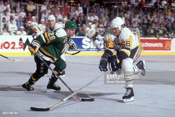 Mario Lemieux of the Pittsburgh Penguins skates with the puck as Shawn Chambers of the Minnesota North Stars defends during the 1991 Stanley Cup...