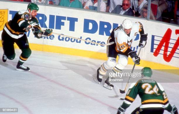 Mario Lemieux of the Pittsburgh Penguins skates with the puck as Chris Dahlquist and Mark Tinordi of the Minnesota North Stars defend during Game 2...