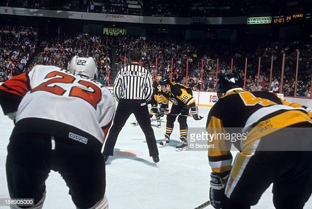 Mario Lemieux of the Pittsburgh Penguins waits for linesman Kevin Collins to drop the puck for the face-off during an NHL game against the...
