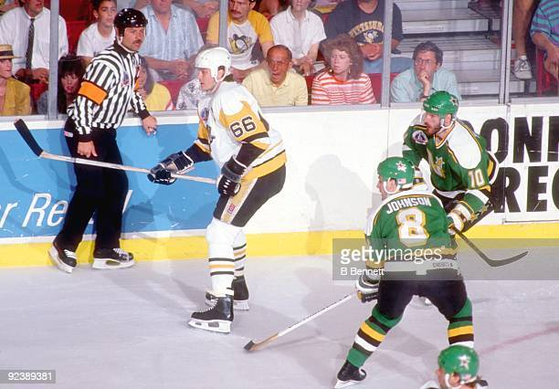 Mario Lemieux of the Pittsburgh Penguins waits for the pass as Jim Johnson and Gaetan Duchesne of the Minnesota North Stars defend during Game 1 of...