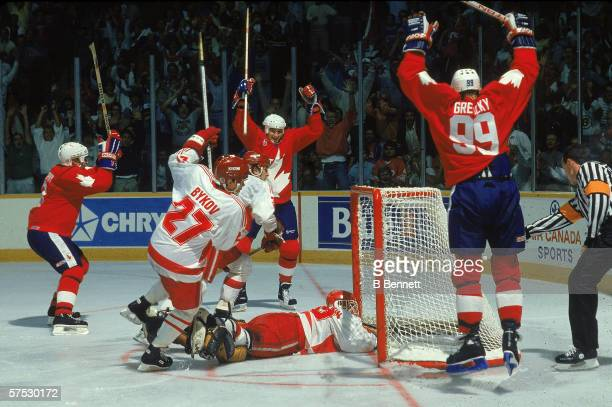 Mario Lemieux teammate Wayne Gretzky and Larry Murphy raise their sticks in the air and celebrate the game winning goal scored against Team Soviet...