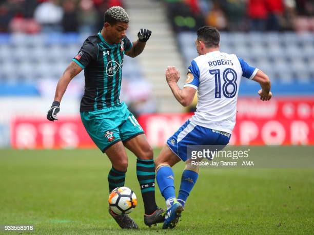 Mario Lemina of Southampton and Gary Roberts of Wigan Athletic during The Emirates FA Cup Quarter Final match at DW Stadium on March 18 2018 in Wigan...