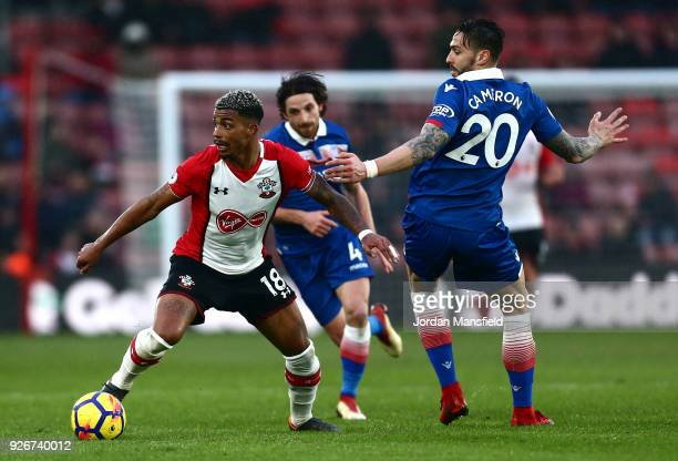 Mario Lemina of Southampton runs with the ball away from the pressure of Geoff Cameron of Stoke City during the Premier League match between...